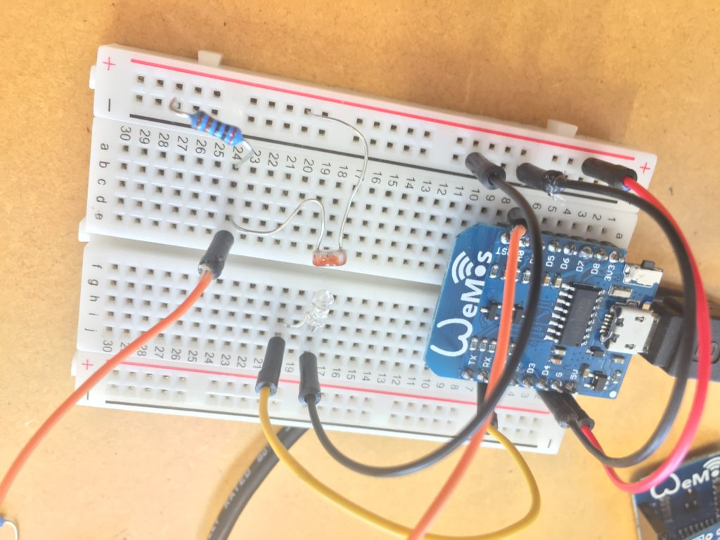 Image showing the Wemos D1 mini microcontroller on a breadboard connected to an LDR (light dependent resistor) and a white LED.